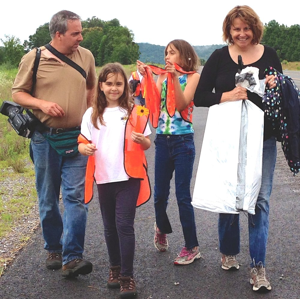 "Above: Husband-wife filmmakers Dave Porfiri and Linda Duvoisin and daughters Harlan, 8, and Jane, 10, return to the Pickin' Up Tennessee RV after a cleanup in Wartburg, Morgan County, on Day 14 of the ""Love the Land, Lose the Litter"" tour in June 2013. Below: With the PUTN RV in the background, cleanup volunteers in Athens in Meigs County, separate recyclable items from collected litter. Of the more than one ton of litter picked up during the month-long tour, roughly half was recycled."