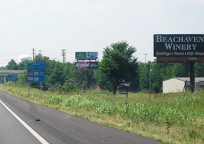 Ever since the legislature passed the logo signs bill in March 1988, the uniform signs have coexisted with billboards on Tennessee's non-urban interstate highways, such as these on Interstate 24 outside Clarksville.