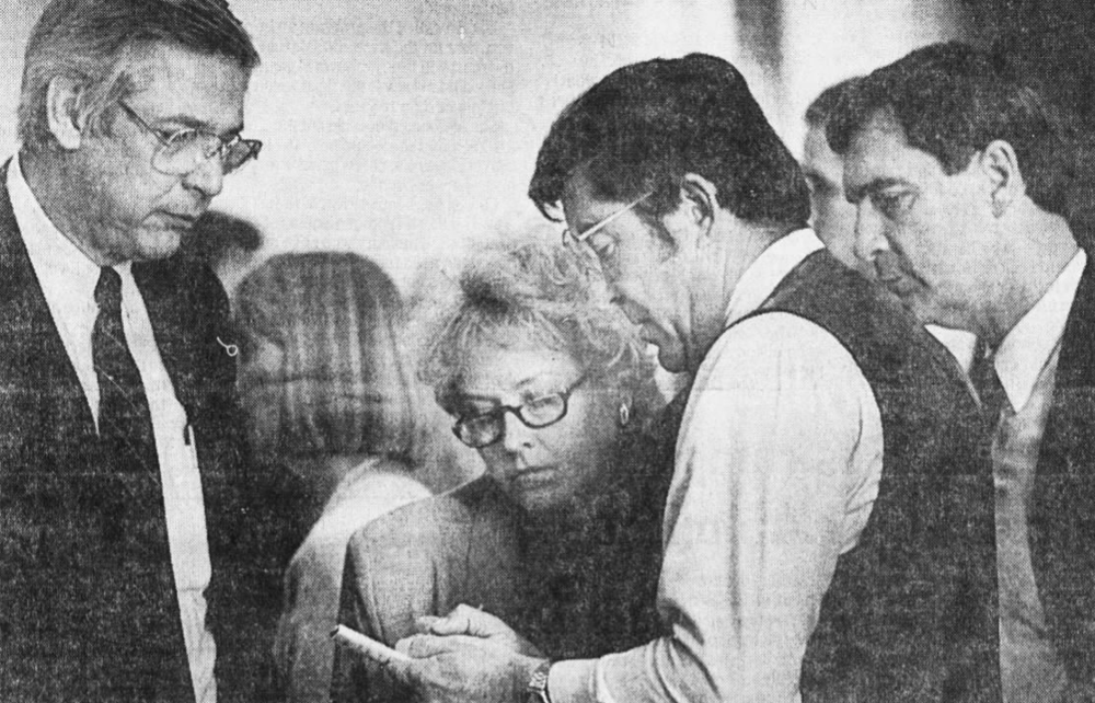 During debate on the logo signs bill in 1988, billboard industry lobbyists Bill Bruce and Felicia Carson (left) confer with Rep. Frank Buck (D-Smithville) and Rep. David Ussery, R-Clarksville. Carson's firm later won the contract to market and manage the logo signs.  Photo credit Bob Roller, The Tennessean