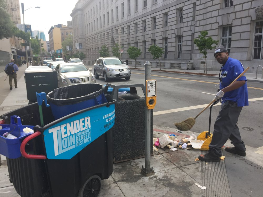 "TLCBD Clean Team member, Maurice ""Mo"" Jackson, removes debris from an overturned trash can."