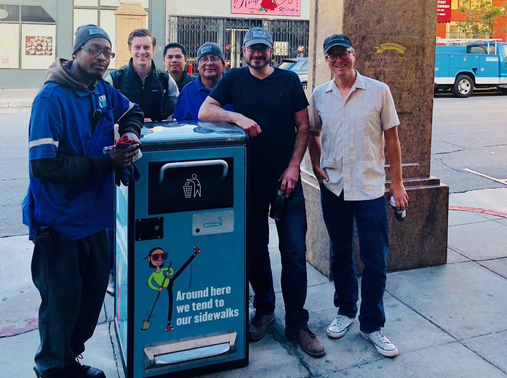 TLCBD staff and partners from Fix It Team and Big Belly company install a new trashcan at the gates of Little Saigon.
