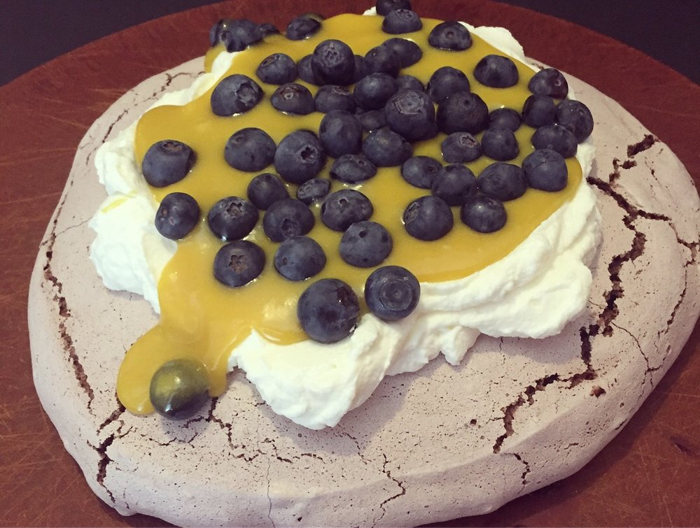 Chocolate pavlova smothered in fresh whipped cream, mango curd, and blueberries. Excessive? We think not!
