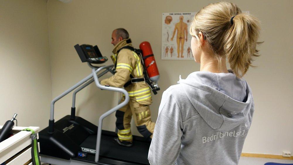Bedriftsfysioterapeut Line Lereng går gjennom sin årlege sjekk av ein røykdykkar ved brannstasjonen på Hydro Årdal.