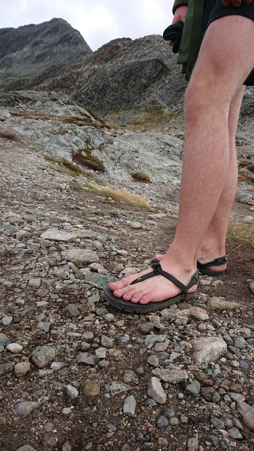 Dette er noko av det fottøyet som blir bruka på Besseggen, men IKKJE det vi anbefalar nokon å gå med! Vi ser helst at du går i ordentlige fjellsko.  Foto: GJENDEGUIDEN