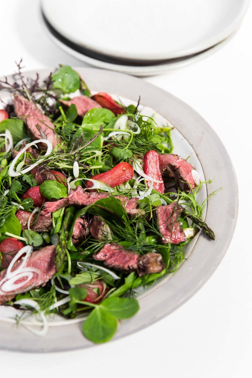 Ingredients - 200g bunch of radishes, washed, trimmed and halved2 tbsp cider vinegar200g bunch of asparagus2 spring onions, trimmed and very finely sliced400g rib-eye steak100g of interesting mixed salad leaves and herbsDressing2 salted anchovy fillets1 small garlic clove½ tbsp Dijon mustard1 egg yolk1 lemon3 tbsp olive oil3 tbsp sunflower oil