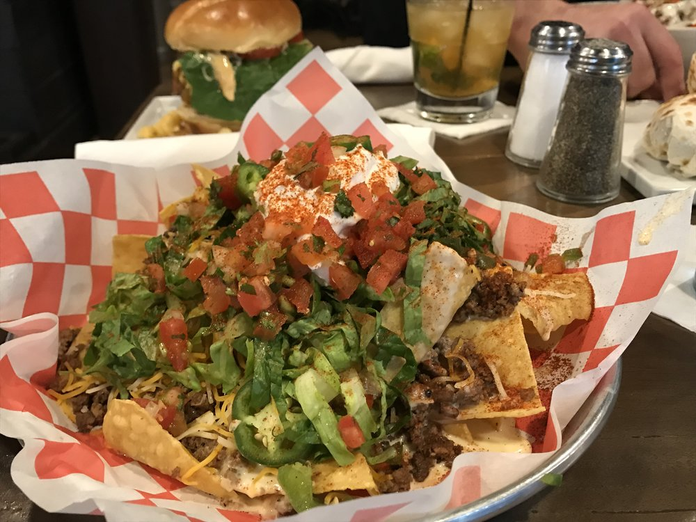 Oliver's Nachos with seasoned ground Beef ( add Smokey Chicken or Black Bean )   Cilantro, Jalapeno's, Lettuce, Mexican Cheese Blend and Sour Cream V | 12