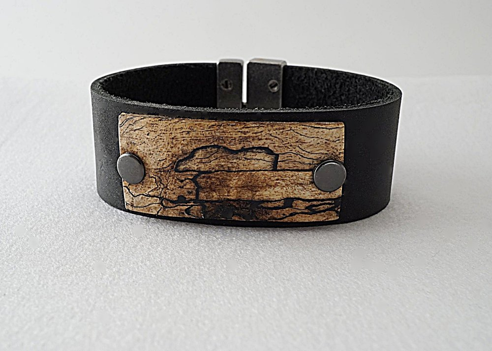 Hand carved spalted tamarind wood riveted onto leather band