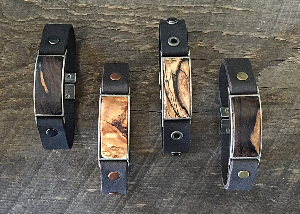Hand carved wood bracelets on leather from left to right: ziricote, buckeye burl, spalted tamarind, and ziricote