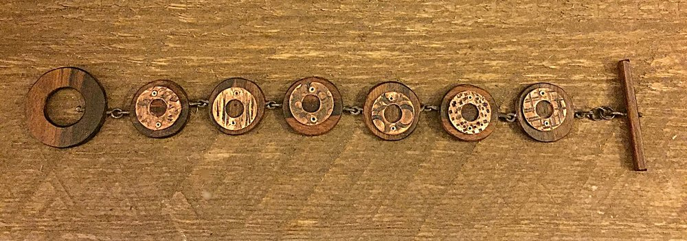 Hand carved bolivian rosewood links with hand stamped copper pieces riveted into the wood