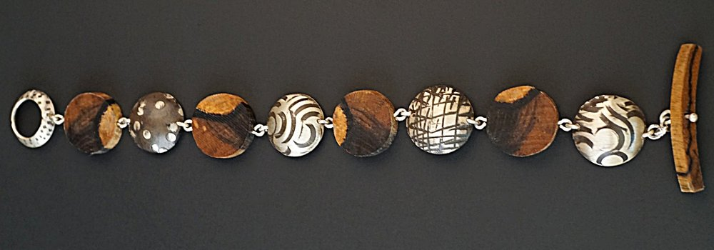 Hand carved black and white ebony wood links rotating with sterling silver hand stamped and domed links