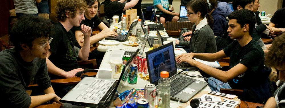 Photograph of a hackathon, where coders, designers and project managers work together intensely on software projects.