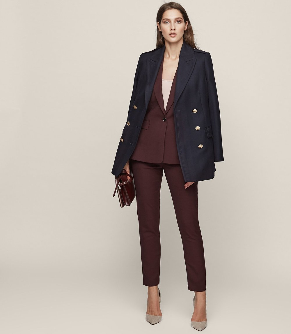 Reiss single button, plunging V  jacket  with slim cut  trouser . Such a gorgeous classic cut, its styled here with a navy pea coat, which is fab. However you can do longer line coats or capes over the top too. Band tees, slogan tees, polo necks and thin knits will all look great under this suit, as well as nothing underneath! Wear with heels, boots or trainers depending on your event.