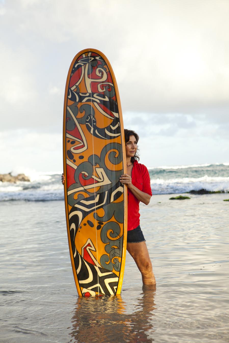 Kim McDonald holding painted surfboard, Kuau, Maui