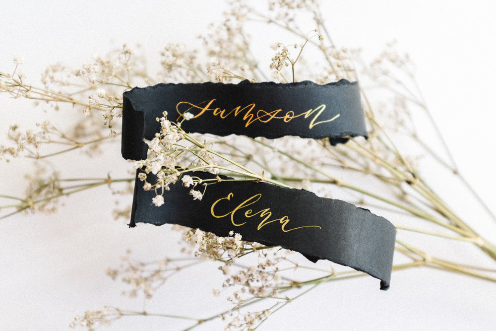Gold calligraphy on ebony scroll place cards