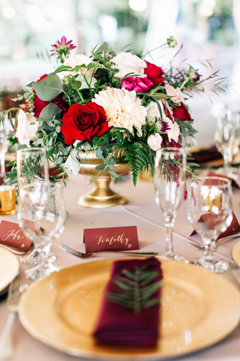 Gold calligraphy on marsala tented place cards  Photo by  Jenna Bechtholt Photography