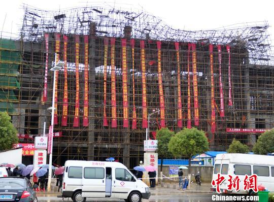 The scaffold collapses at the construction site of a convention center in Dexing City, east China's Jiangxi Province, Wednesday night. Four workers have been confirmed dead.