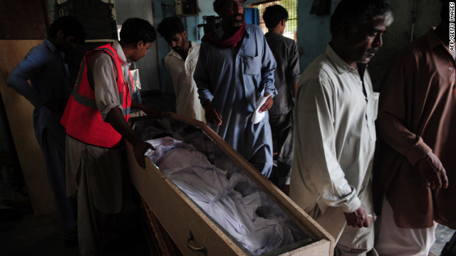 Pakistani men identify dead relatives at the EDHI Morgue in Karachi, a day after a garment factory fire killed more than 250 people.