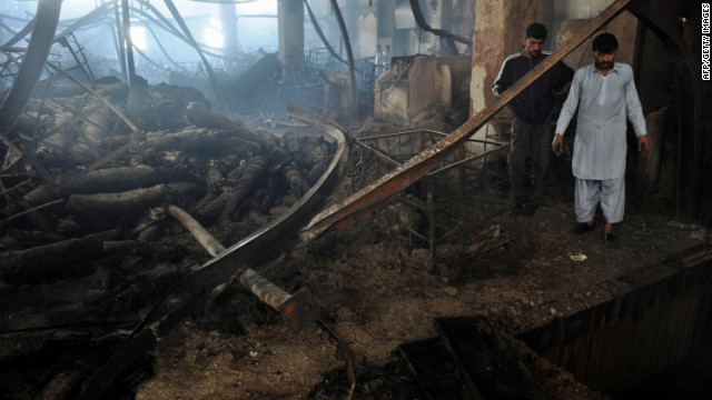 Men stand in the rubble after a garment factory fire in Karachi. Police have registered a murder case against the owners of the factory, where at least 258 people died Tuesday.