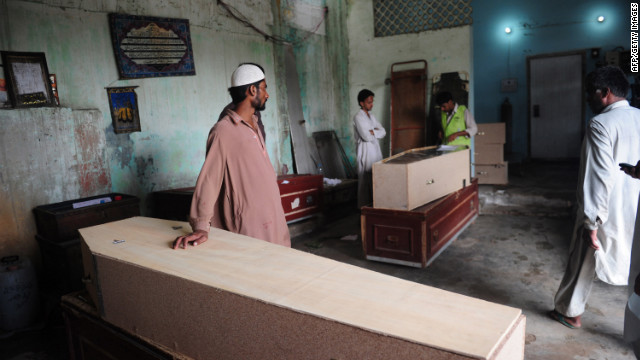 Pakistani men wait alongside coffins for the bodies of their relatives who died in the garment factory fire.