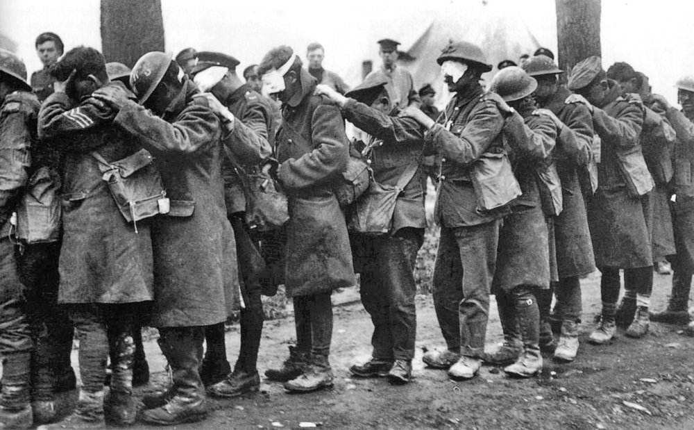 Image from  Wikimedia Commons ;  British 55th (West Lancashire) Division  troops blinded by tear gas await treatment at an Advanced Dressing Station near Bethune during the  Battle of Estaires , 10 April 1918, part of the German offensive in Flanders.
