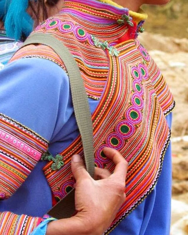 Hmong women's Top with hand embroidery. (Close up) . Hmong groups are identifiable by the contours of their Jacket lapels which take various forms. In Striped, White, and certain Blue Hmong communities, women's lapels are designed as wide embroidered bands that follow the straight front edges of their jackets. There are two design variations for this diagonal panel in Blue Hmong women's jackets: either overlapping panels with three large zigzag points or panels with up to seventeen small jagged zigzag points, both edged in red. .  #hmongclothes #hmongtop #vietnam #traditionalclothing #embroideredlapel #colorfulembroidery #colors #traditionalstyle #preservetraditionaldesigns #sisterhoodoflolalovecargo