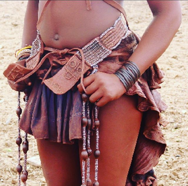Himba Women Of Namibia. . Himba women smear their body, hair , clothes and jewelry in a red paste called otjize  The otjize is a mixture of butterfat, ochre pigment and scented resins extracted from the Commophora wildii, the Himba women use it to protect themselves from the extremely hot and dry climate of the  Kaokoland and sunrays; it is also a good repellent against insect bites. It is considered an aesthetic beauty cosmetic. It gives the skin and hair a terracotta-like reddish colour . They wear a simple skirt of ombuku goat hide, adorned with leather adornments , leaving their breasts exposed and wearing just leather sandals. . #himbawoman #himbatribeswoman #indigenouswomen #traditionalstyle #leatheradornments #lolalovecargostyle #sisterhoodoflolalovecargo #preservetraditionalcraftsmanship