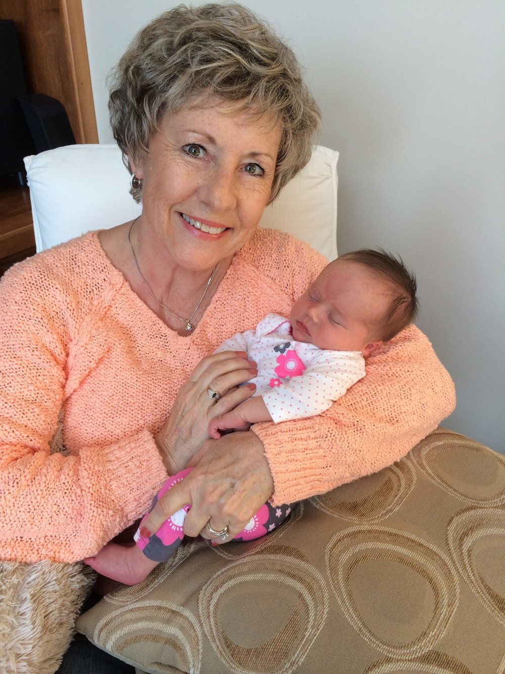 "This is my mom with her granddaughter, Sydney. This photo was taken less than a week after she had lung surgery, and shortly after Syd was born. She was in a ton of pain and still smiling. If you asked her, she'd say, ""Of course I'm smiling. I'm holding my new granddaughter."""