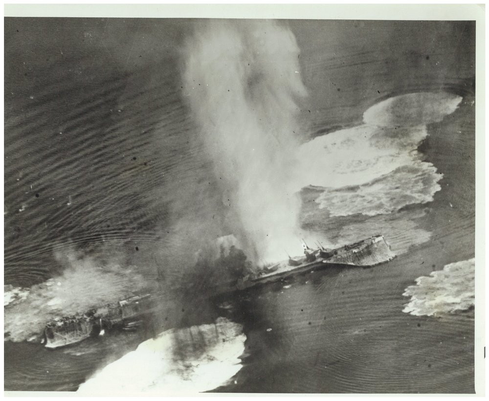 The heavy cruiser  Tone , exposed to bombardment by the US Navy aircraft carrier planes on July 24, 1945. The crew is firing antiaircraft weapons, and she is surrounded by great geysers caused by the close-falling bombs. The air attack was repeated on July 28, and the Tone sank with serious damage.