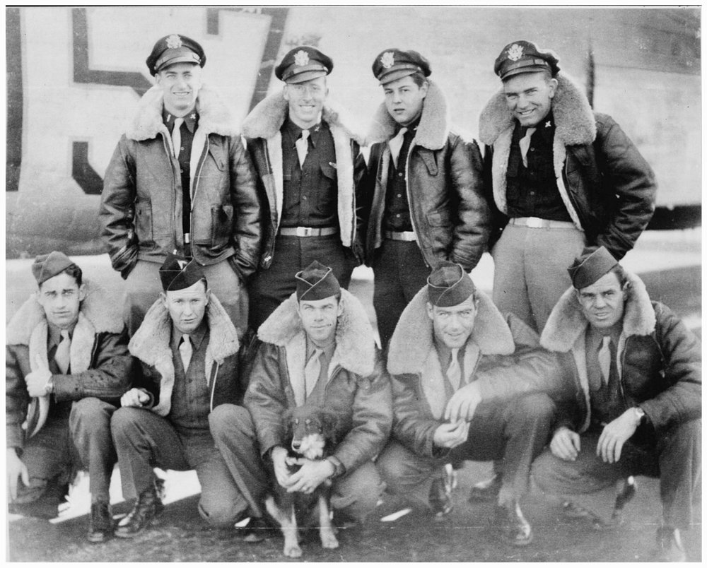 Top:  The  crew of the  Lonesome Lady  , photograph taken half a year before their sortie on 7/28/45. Front row from left: Sgt. Hugh Atkinson, Sgt. Buford Ellison, Blacky the mascot dog, Sgt. William (Bill) Able, Corp. John Long, and Frank Baker, who did not board due to illness and was replaced by Sgt. Ralph Neal.)   Back row from left : 2nd Lt. James Ryan, 2nd Lt. Durden Looper, 1st Lt. Thomas Cartwright, 2nd Lt. Pedersen (Photo courtesy of Mr. Francis Ryan )