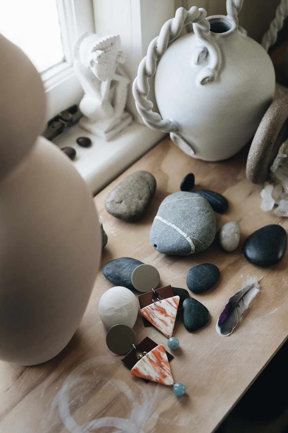 The Cleopatra Earrings in Tan sitting amongst found objects and ceramics in Nicolette's studio