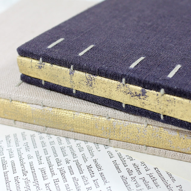 Coptic bound books with distressed gold linen spines by Kaija Rantakari / paperiaarre.com