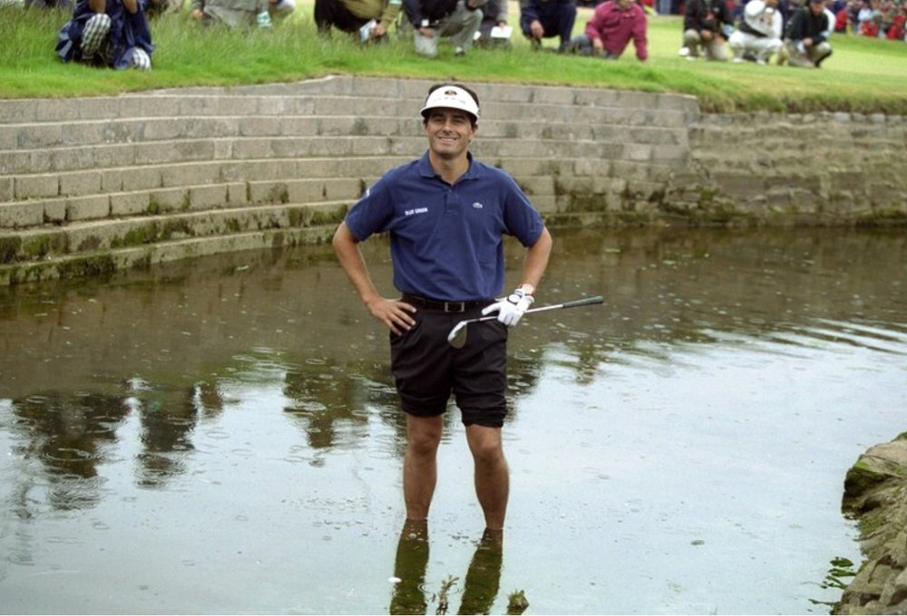 you idiot...  The 1999 Championship, Carnoustie's first since 1975, featured a climax so extraordinary, so unexpected, that it will never be forgotten. It resulted in Lawrie becoming the first Scotsman to win the Open on native soil for 68 years but also made Frenchman, Van de Velde, headline news all over the world.  The records show that Lawrie, the first qualifier to win the Open since the R & A started to give exemptions in 1963, won the title after recording rounds of 73,74.76,67 and then beating Van de Velde and former champion, Justin Leonard, in a subsequent four hole play-off. However, what the bare facts don't explain are the incredible scenes witnessed on the 72nd hole.  To set the scene, Lawrie, then ranked 159th on the official World Rankings, had started the final round ten shots out of the lead. Despite a fine four under par 67, he was still three shots behind Van de Velde as the Frenchman mounted the last tee but, sensing something might happen, continued to practise his putting as a worldwide audience measured in millions watched in amazement as Van de Velde proceeded to implode.  Lawrie deserves huge credit for the manner in which he played, both during the last round and in the resultant play-off but, in the end, he still could not have prevailed had it not been for Van de Velde perpetrating one of the biggest collapses in sporting history.  Needing only a double bogey six on the final hole to become the first Frenchman to win the Open for 92 years, Van de Velde ran up a catastrophic triple bogey seven, even having to hole a brave 10-foot putt to get into the play-off.  What transpired left the eloquent BBC golf commentator, Peter Alliss, almost lost for words. The Frenchman hit his drive right off the tee, finding dry land, albeit on a peninsula guarding the Barry Burn. From there, he could have hit wedge, wedge onto the green but, instead, elected to go for the green in two. Sadly for him, his second shot did not come off as he had envisaged. Instead, it hit the upper tier of a grandstand and rebounded into the deep rough.  That was the start of Van de Velde's problems. Next, the horrified gallery watched as his third shot came out softly and went into the burn in front of the green. After that, the episode became almost surreal. To begin with, the Frenchman chose to take off his shoes and roll up his trouser legs before jumping into the water to see if he could hit his submerged ball. Finally, as the water lapped around his ankles, sense prevailed. Van de Velde took a drop in the rough but then hit his fifth shot into the bunker guarding the right of the green. Under the circumstances, he displayed exemplary fortitude to blast his sixth shot out to ten feet and then hole the resultant putt. Click  here  to watch the 18th unfold.  Sadly, though, Van de Velde's chance to win the Claret Jug had gone. On the first play-off hole, clearly still in torment over what had happened ten minutes earlier, he hit his tee shot into a gorse bush leaving Lawrie and Leonard, the 1997 champion, to battle it out.  In the end it was the unheralded Scotsman who prevailed. He moved into the lead when he holed a 12-foot birdie on the 17th, the third play-off hole, and then sealed his first major title when he hit his second shot to three feet for another birdie on the 18th.