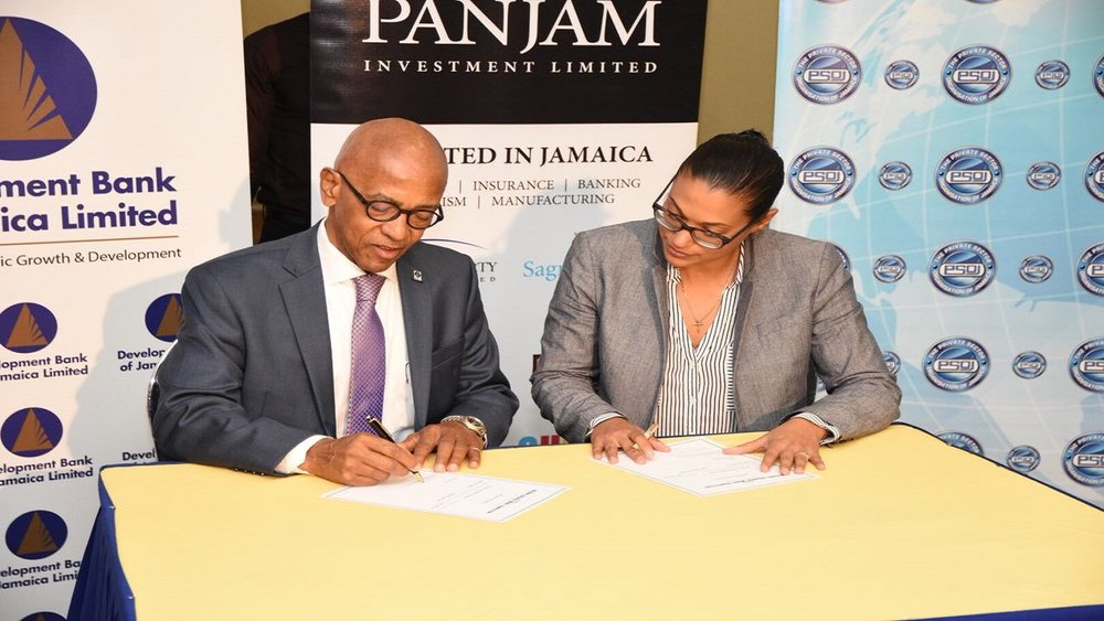 DBJ's Managing Director Milverton Reynolds signing the official sponsorship agreement with Platinum Sponsor PANJAM Investment's VP - New Business Development and Strategy, Joanna Banks.
