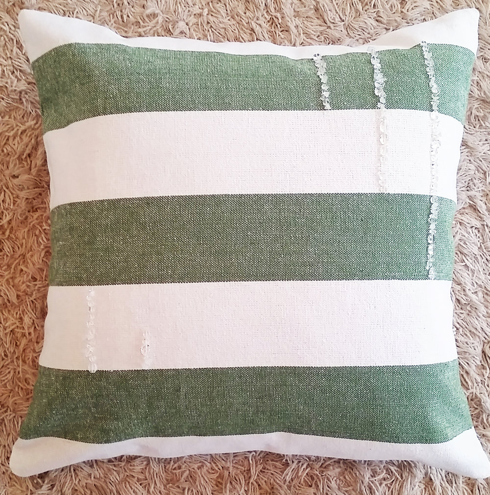 Green and white striped pillow with quartz crystal
