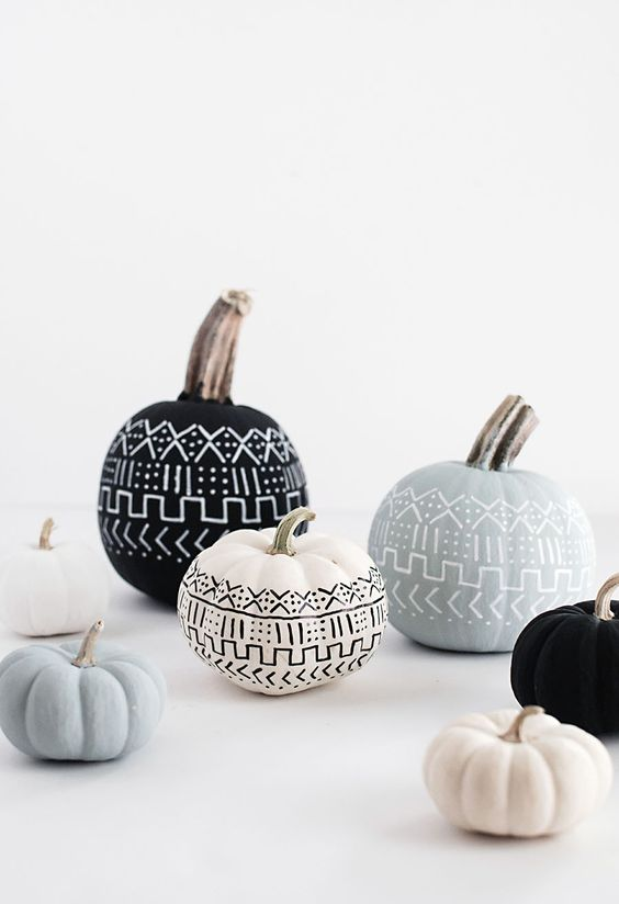 Paint your pumpkins pretty pastel colors and black.  Then with a thin paint brush paint geometric designs on them.