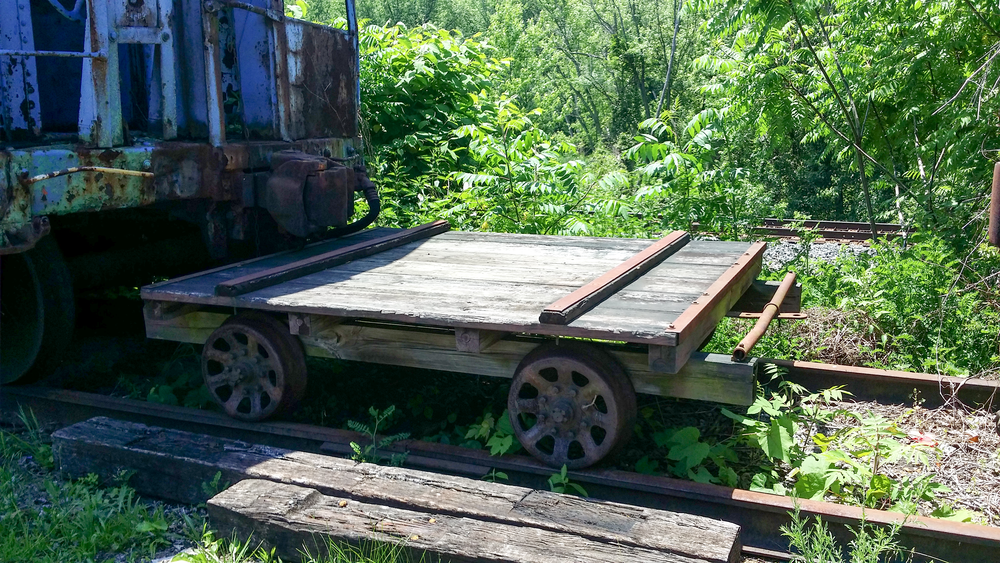 A small railroad cart sits between the Conrail Cabooses.