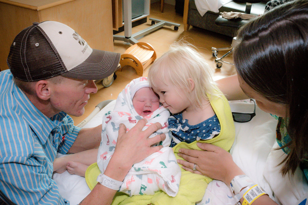A newborn baby sister being held by big sister surrounded by mom and dad
