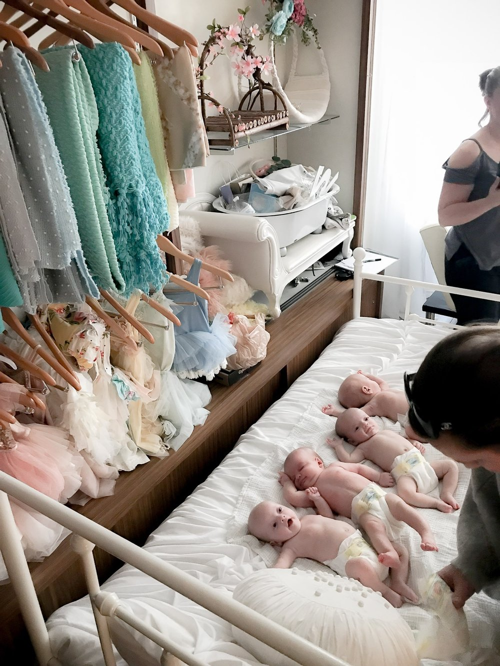 Four babies laying on a bed waiting to be swaddled for newborn shoot