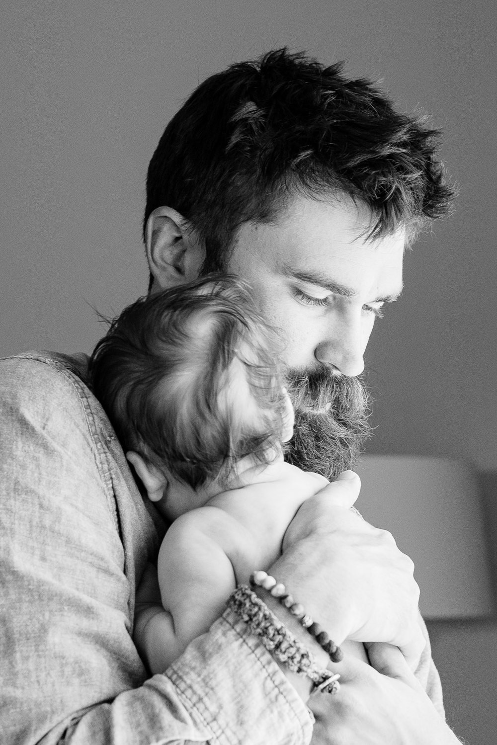 Black and white image of daddy holding his newborn baby girl on his shoulder.