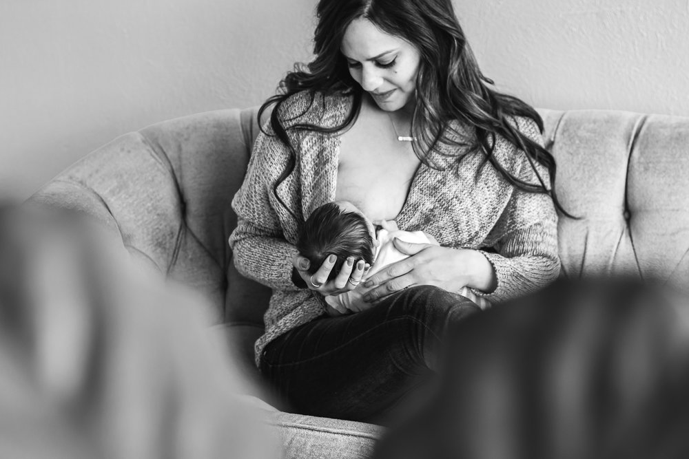 Black and white of mother breastfeeding her newborn son.