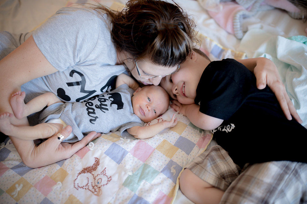 Mommy and big brother snuggling with newborn baby sister.