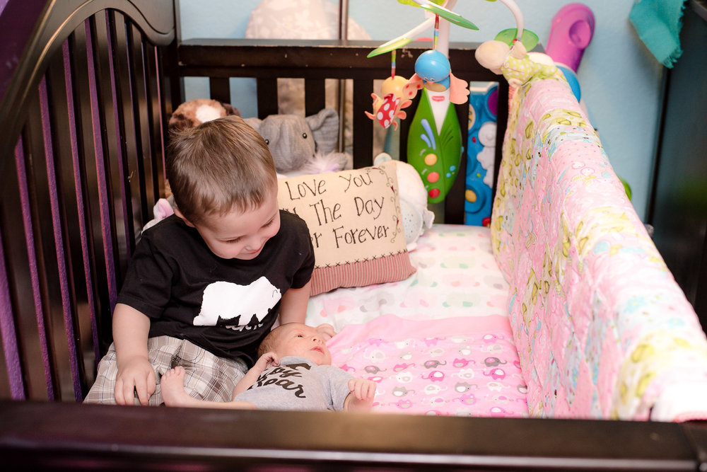 Big brother climbed into crib to be with his new baby sister.