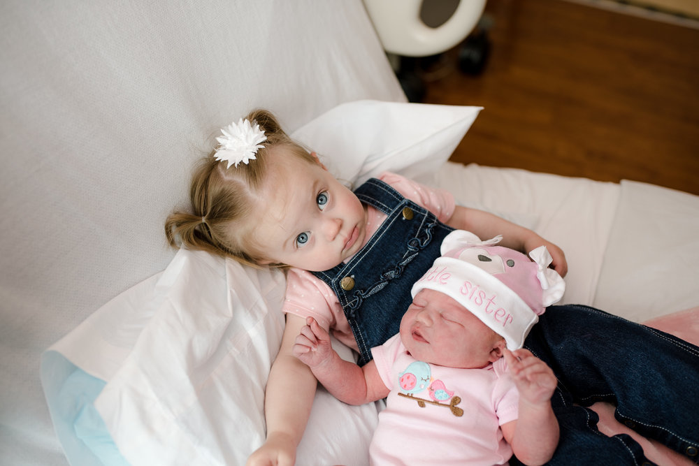 Big sister is not quite sure what to think of little sister.