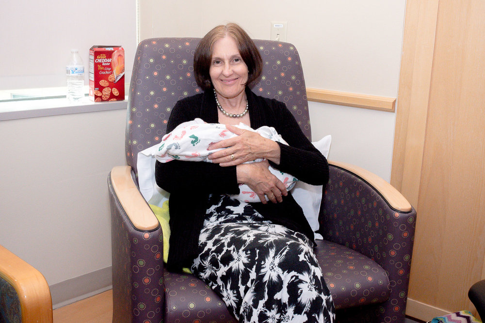Big smile on Grandma's face as she holds new granddaughter for the first time.