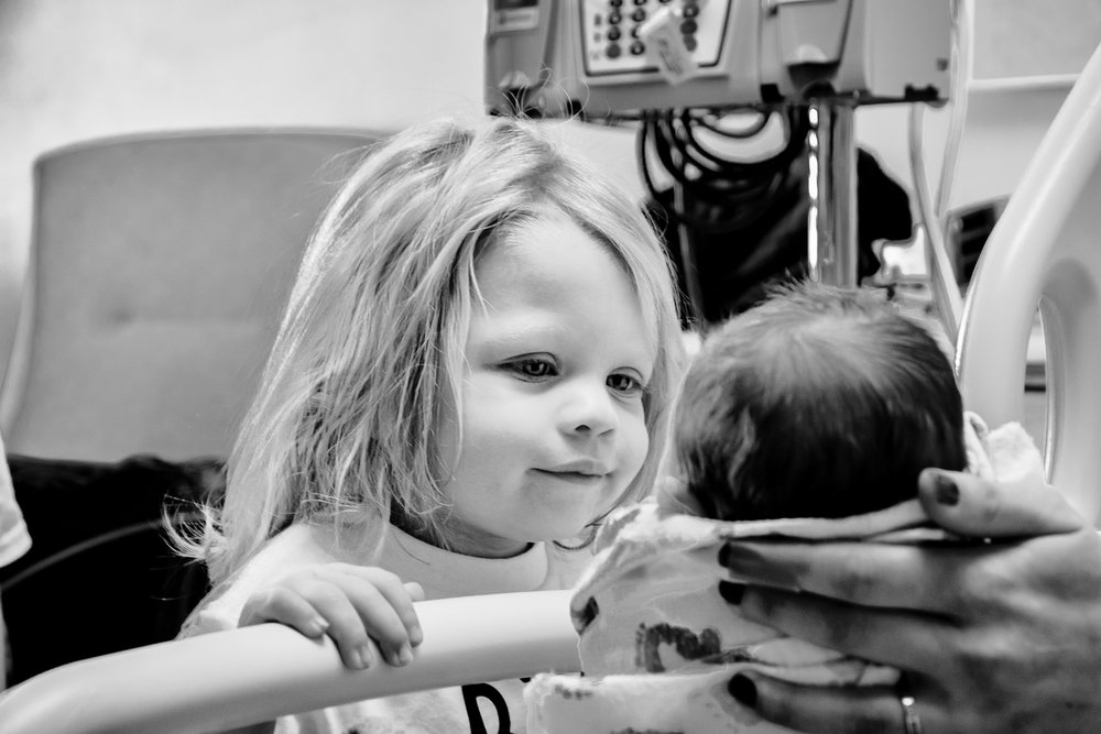 Black and white image of  sweet big sister seeing little brother for the first time.