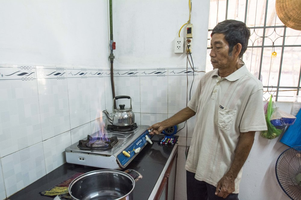 Farmer Than shows us how his cooking stove works using the captured methane fuel.
