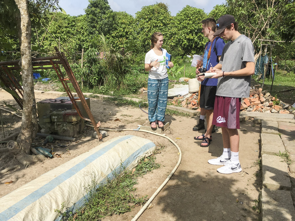 Students have a discussion next to a biogas collector. The visible hose connects to the home, powering the cooking stove.