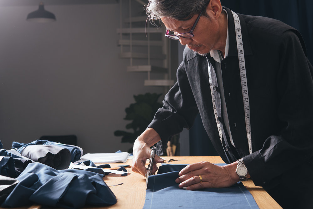 Veteran tailor Mr. David cutting out a suit pattern