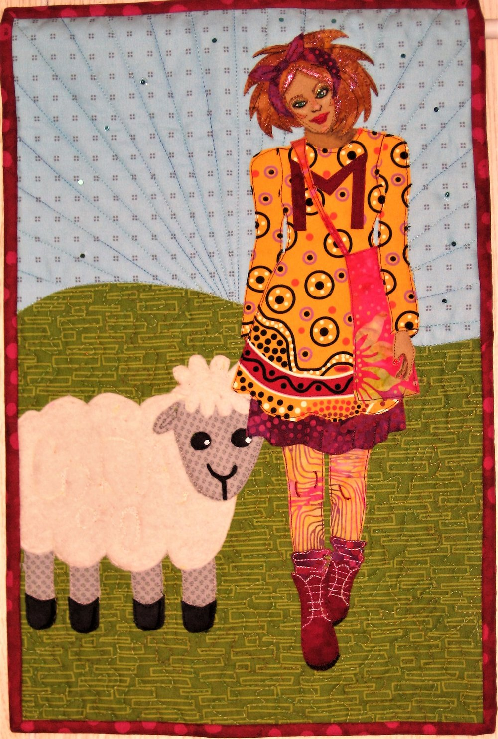 "My Facebook art quilt group Art Quilts Around The World has it's reveal today. The theme is nursery rhymes with a back story or plot twist. I chose Mary Had a Little Lamb and the lamb was co-dependent and that's why she followed Mary to school!! Haha!! I decided to make Mary a high school student with a cute fit and flare dress and petticoat, leggings, slouch sox and Doc Martin boots! I selected the local Menominee high school colors of maroon and gold for the color scheme of Mary's outfit. Locally anyone supporting the local high school wears a maroon ""M"" on the front of their dress/tee shirt etc. The ""M"" could also represent Mary's first name initial.  The lamb was created by me Googling lamb clip art since I didn't really know what a lamb looks like. For the fleece I used quilt batt-not ""as white as snow"" but I loved the fuzzy texture! I thread painted CoDA.org on the lamb's body to share about the national organization which helps people (lambs?!) with co-dependency.  I had fun stitching the details of Mary's garment especially the boot details."