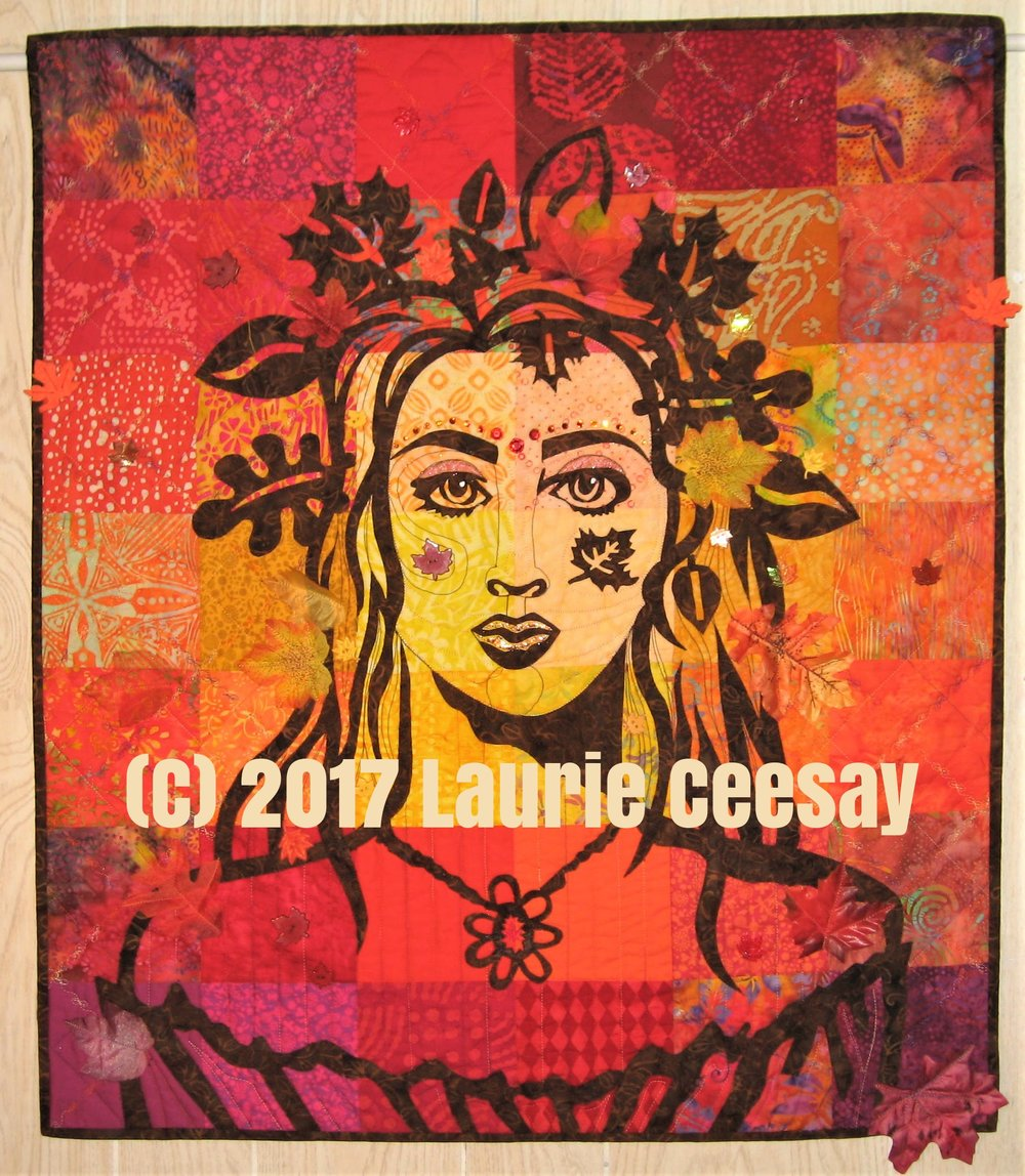 "This is my Autumn version of my newest portrait quilt pattern ""Earth Mother."" I selected golds, oranges, reds and a few plums for the background squares. I used charm packet pre-cut squares of batik, commercial cottons and even a few solids. I selected a dark spicy brown batik for the raw edged fused applique.  Again, as in the first ""Summer"" version, I quilted the background with the same leave motif stitch and variegated thread. I quilted the face, the neck, hair and dress. Then I fused the leaf appliques that form a crown around the hair.  I have been collecting lots of leaf themed embellishments. I found several silk leaves (maple and oak) at The Dollar Store, sheer leaves, plastic leaf buttons, felt leaf buttons, iridescent leaf sequins, chunky leaves that were glued onto the quilt and a leaf trim in which I cut one leave and glued it to the center of the pendant. All of my embellishments are matched to a color on the quilt which allows me to add alot of items without it looking garish."